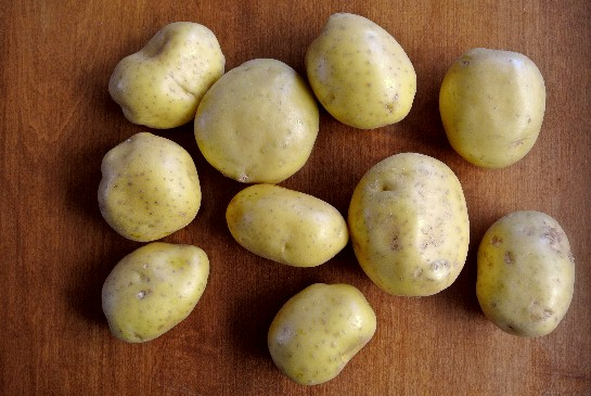 Yukon Gold potatoes for the Mashed Potato Casserole are set out on an oak table to show off they're golden color.