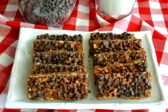 Chewy Chocolate Chip Bars are lined up in two rows on a white square plate..
