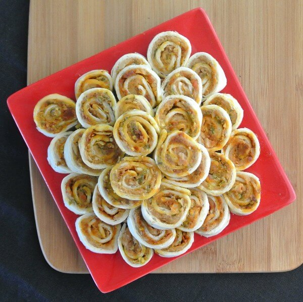 Pesto Tortilla Rollups are pictured from above. A pyramid of rolled tortilla slices filled with refried beans and pesto.