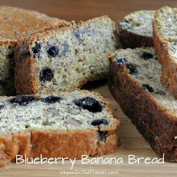 Blueberry Banana Bread is a close photo of the inside cut of the banana bread with many slices tilited and piled on each other.