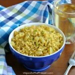 Easy Curry Rice is golden and in a cobalt blue bowl sitting next to a blue plaid cloth napkin.