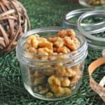 Slow Cooker Maple Glazed Walnuts are in a canning jar with ribbon on the side so that it can be wrapped for a holiday gift.