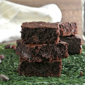 Three brownies stacked on each other on a green mat.