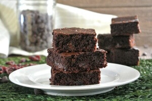 Three chocolaet brownies on a white plate with more behind.