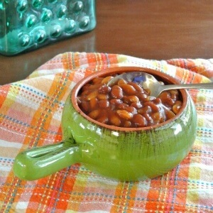 Slow Cooker Baked Beans are cooked with a little bit of a kick added. By dinner time they are perfection and ready to be served to the whole family.