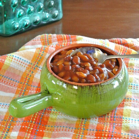 Crockpot baked beans are in a gren handled bowl on an old fashioned napkin.