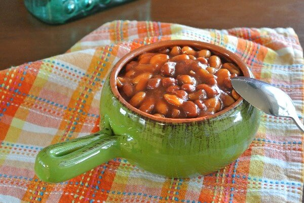 A green handled bowl if fill with baked beans on a plaid napkin.
