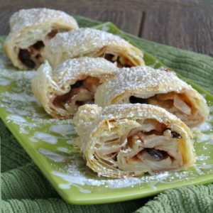 A row of staggered thick slices of apple strudel are sprinkled with powdered sugar.