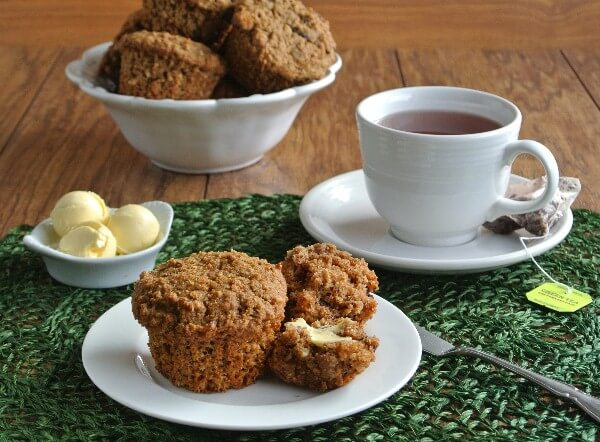 Healthy Morning Muffins are plated and buttered with a cup of green tea on the side.