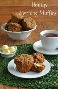 Healthy Morning Muffins are split open and sitting with balls of dairy-free butter and a cup of coffee.