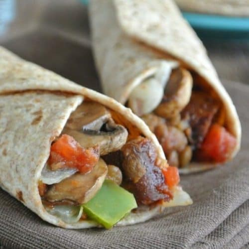 Two burritos side by side with veggies showing out the end.