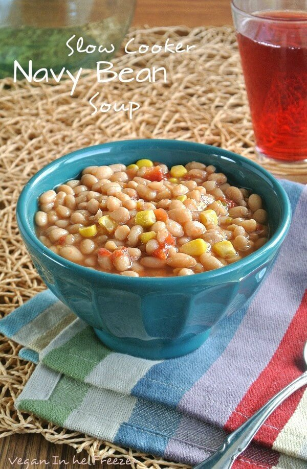 Slow Cooker Navy Bean Soupis in a turquoise bowl and on a colorful striped napkin including turquoise. The navy beans are waiting for you to take a big bite.