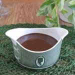 Homemade Chocolate Syrup is filling a green and white transferware sauce boat. Sitting on a forest green mat.