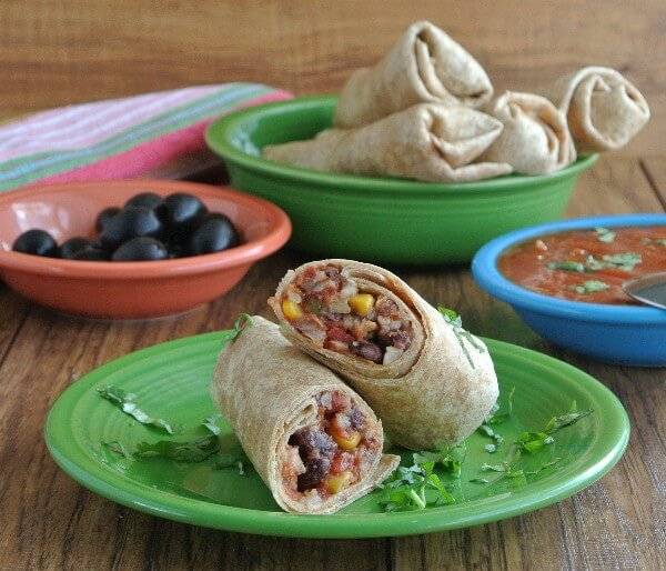 Slow Cooker Black Bean Burritos are sliced in half and sitting on a bright green plate. Black olive, salsa and a bowl full of burritos are in the background.