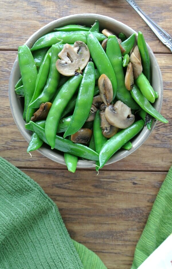 Overhead view of sugar snap peas with mushrooms against a wooden tabletop.