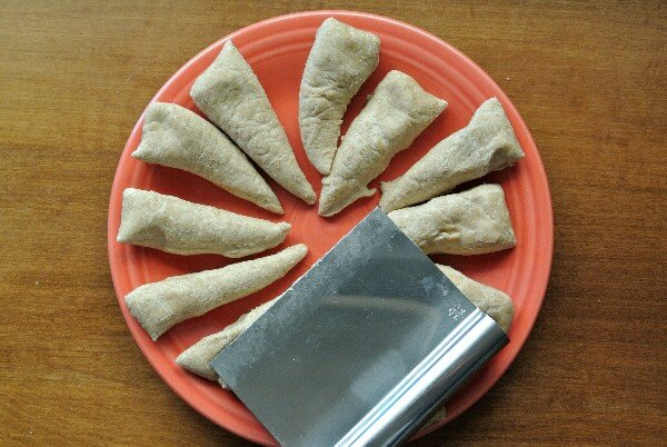 Vegan Empanadas dough is laying on a plate as a flat round and cut into 12 evenly sliced triangles. Read to be rolled out.