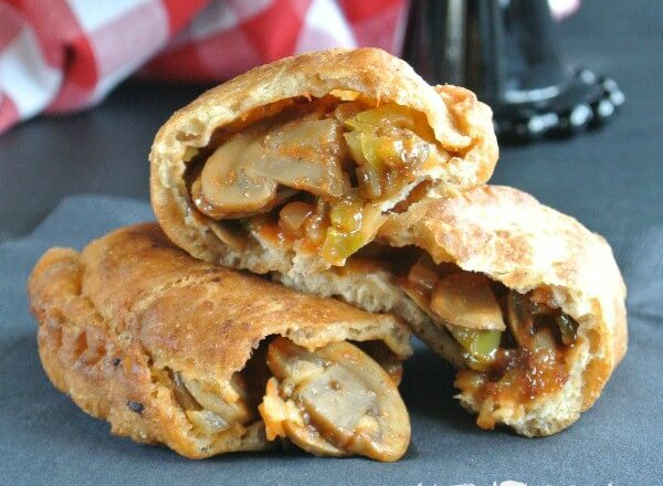 Wide photo of empanadas opened and givin a close of view of the mushroom and sofrito filling.