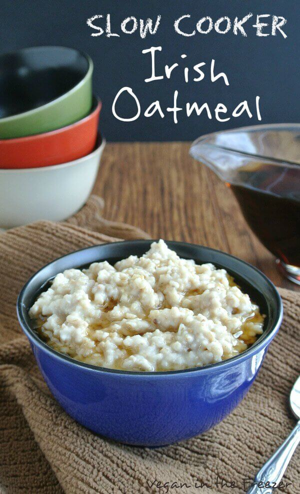 Slow Cooker Irish Oatmeal is in a cobalt blue bowl with maple syrup floating around the edges.