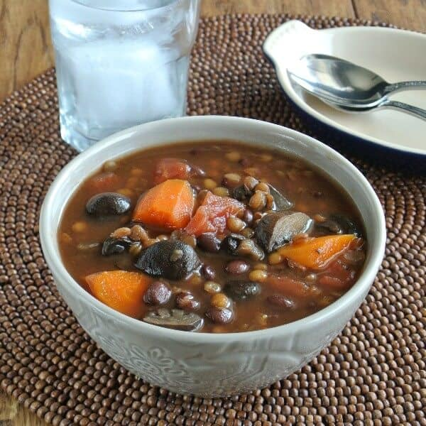 A bowlfull of rich dark soup filled with vegetables and legumes.