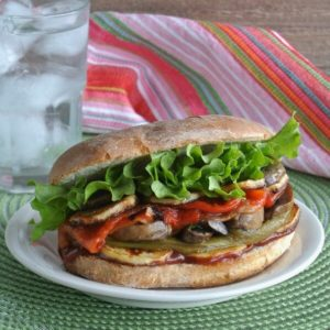 Roasted Vegetable Sandwich is piled hign with oozing roasted vegetables in colorful layers.