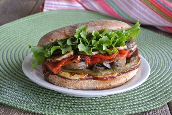A wide photograph of vegetable layers all on a sandwich bun.