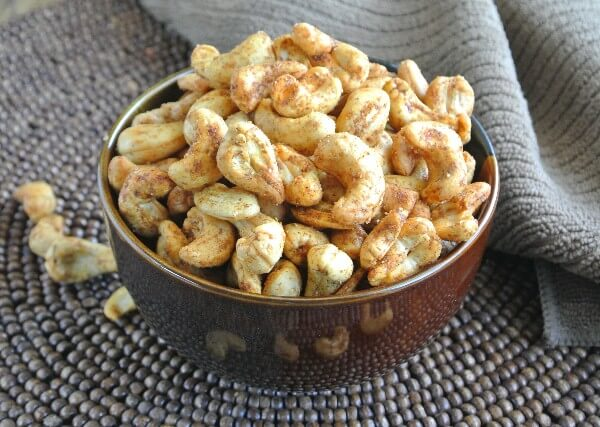 The Best Slow Cooker Spiced Cashews are golden and tilted forward in a chocolate colored bowl and is sitting on a dark brown beaded mat.