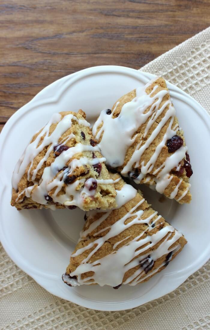 Gluten-Free Cranberry Orange Scones are the perfect treat. Citrus, cranberry and a sweet glaze will make you want to serve these over and over. A classic combination!