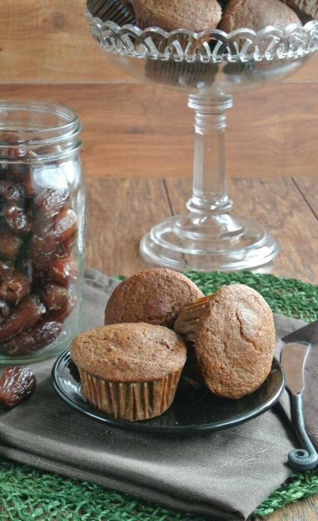 Three muffins on a white plate with a jar full of dates behind.