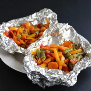 Small snapped and sliced vegetables areare piled high in an open foil package.