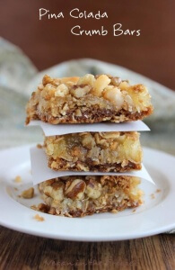 Pina Colada Crumb Bars are a creamy yellow color and the squares are stacked three high and seperated with asmall square of parchment paper.