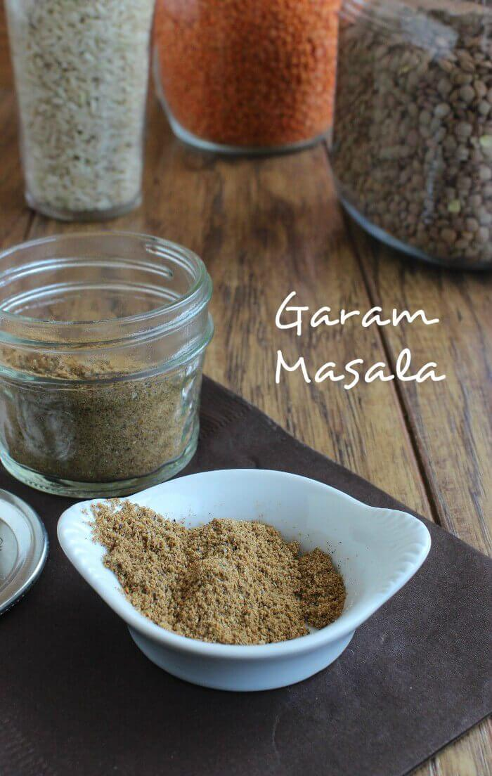 Photo of garam masala is dished up in a small white borl with a larger half pint jar behind with more garam masala inside.