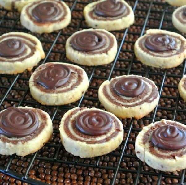 Chocolate Pinwheels with a chocolate swirl topping and sitting on a wire rack.