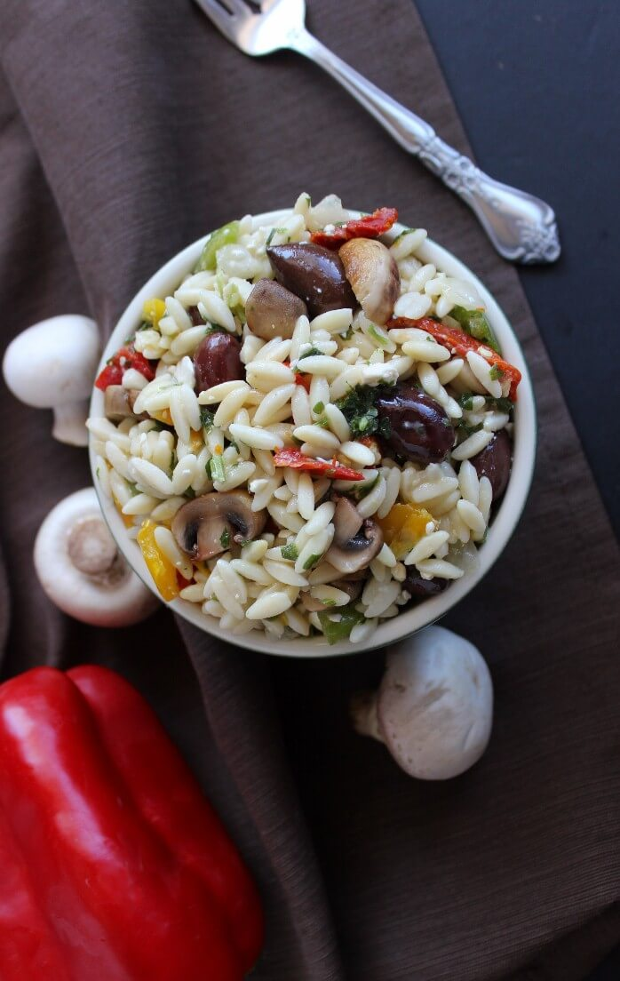 Greek Orzo Salad with an overhead view surrounded by fresh mushrooms and a bright red pepper.