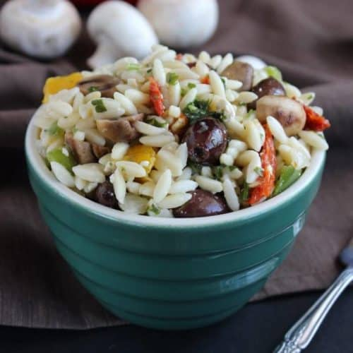 Small orzo pasta is tossed with olives and mushrooms and served in a green bowl.
