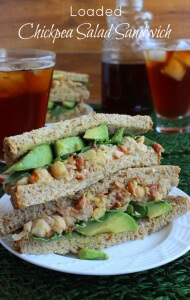 Loaded Chickpea Salad Sandwich is cut in half and stacked double high. Soft wheat bread avocado and chickpea salad are thickly layered.