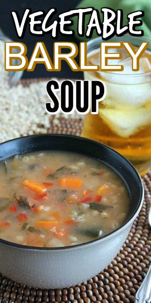 Extra long photo of a closeup of barley soup with vegetables showing through the flavorful broth. A glass of iced tea is sitting next to the bowl.