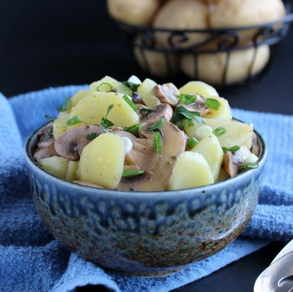 Pared potatoes and sliced mushrooms fill a blue speckled bowl with an iron basket of unpeeled potatoes behind.