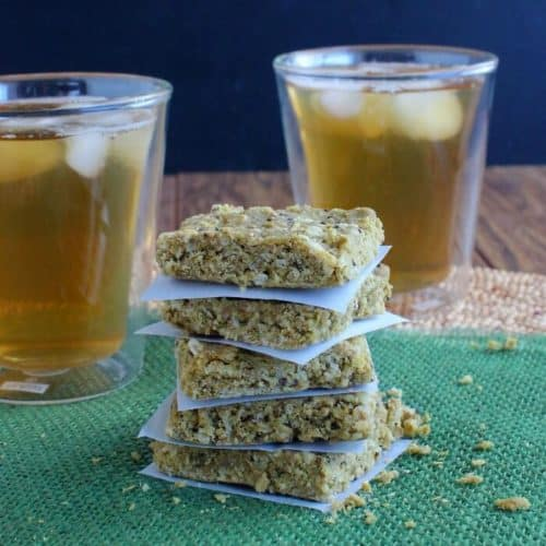 Almond Butter Protein Bars are sitting on a green mat and are cut into squares. Stacked 5 high infront of 2 glasses of iced tea.