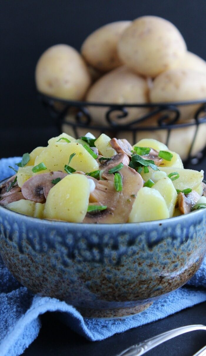 Mushroom Potato Salad in a wedgwood blue bowl closeup photo of potatoes and mushrooms mixed in the salad.
