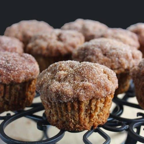 Cinnamon Apple Crisp Muffins are sitting on as black trivet.
