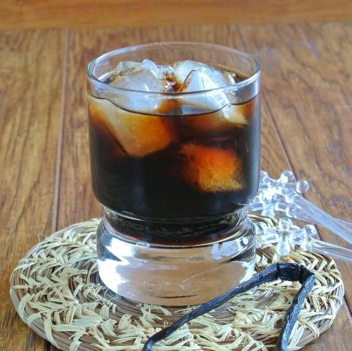 Homemade Kahlua is ina a clear fat footed glass and is filled with ice and sitting on a pine needle woven mat.