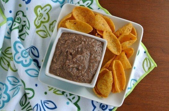 A square bowl full of dip is sitting on a square plate full of chips.
