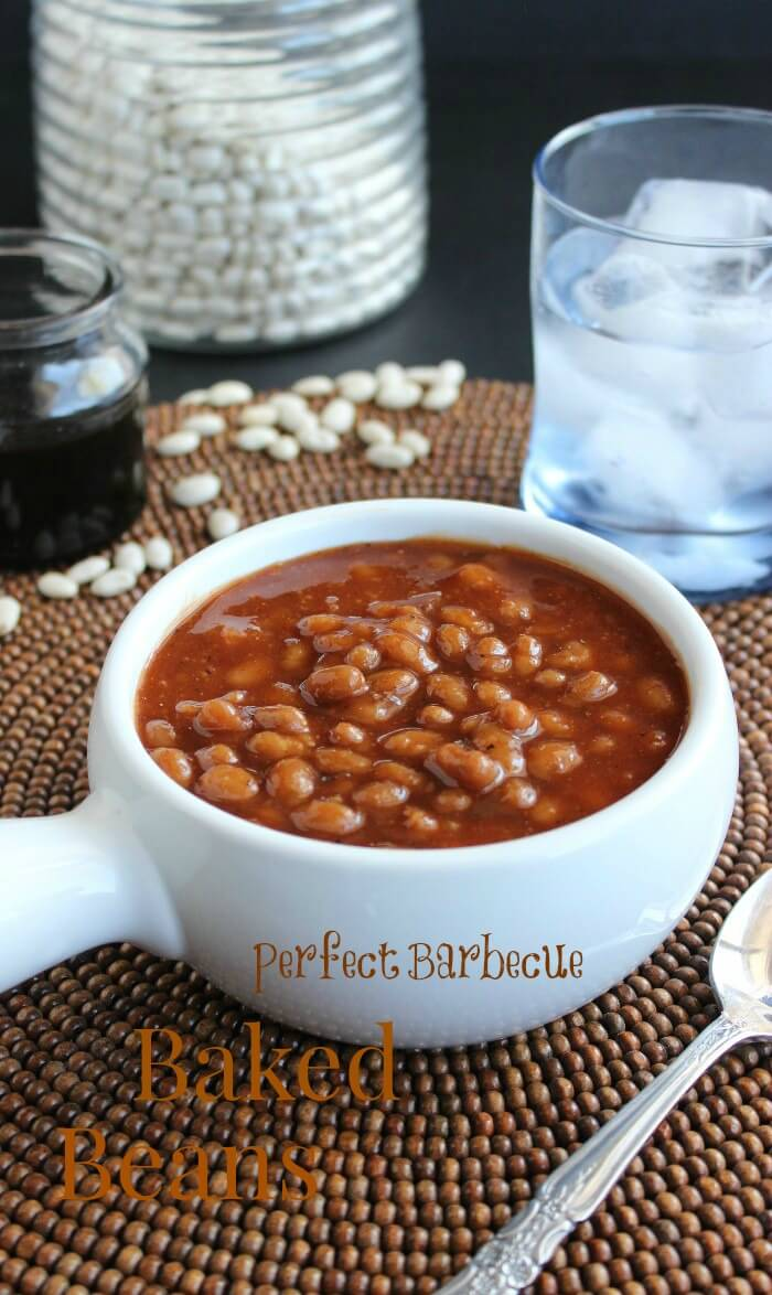 A white handled bowl filled with rich old fashioned baked beans and text above.