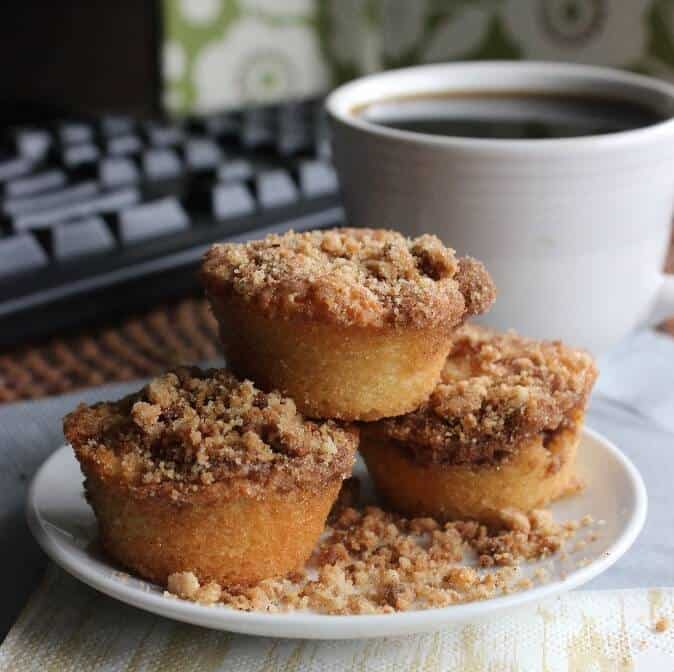 Cinnamon Streusel Mini Muffins are stacked three high on a white plate with streusel all around.