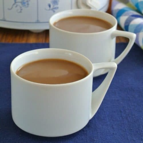 Irish Cream Coffee is filling a white cup with another angled behind.