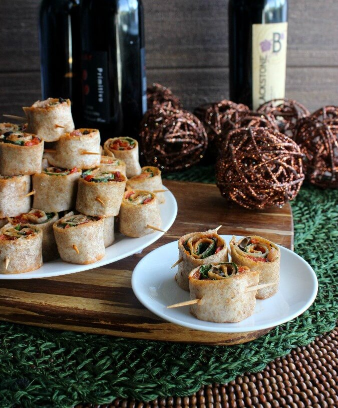 Spicy Tortilla Rollupsare stacked as a pyramid surrounded with dark earthy background colors and napkins on the side.