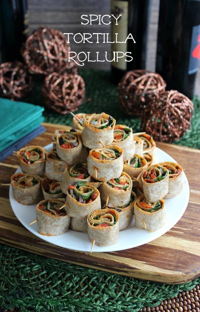 Spicy Tortilla Rollupsare stacked as a pyramid surrounded with dark earthy background colors and different bottles of Tobasco flavors.