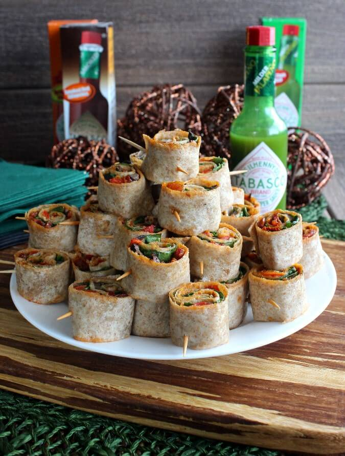 Spicy Tortilla Rollupsare stacked as a pyramid with a small plate with three more rollups waiting to be eaten.