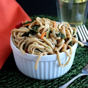 Asian Noodle and Kale Salad piled high and overflowing onto a green mat and cropped square.