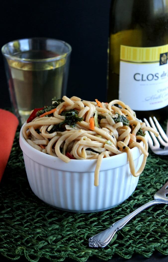 Asian Noodle and Kale Salad has long noodle with some escapiong the bowl. kale is peeking out around the pasta.